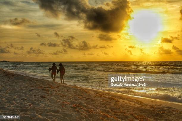 Friends Walking On Shore Against Sea During Sunset