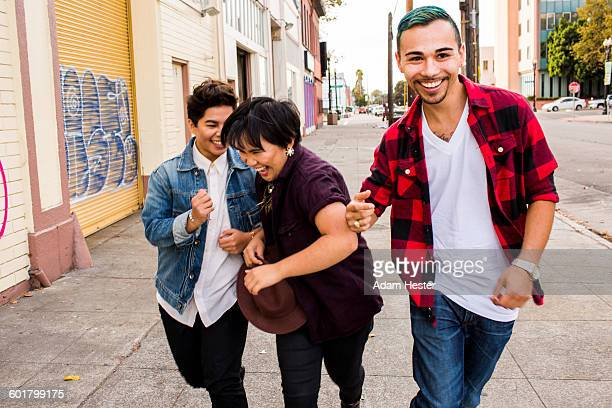 friends walking on sidewalk - oakland california stock pictures, royalty-free photos & images