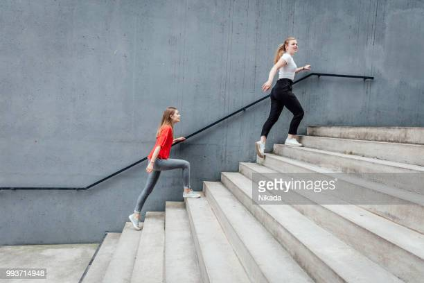 friends walking on stairs by concrete wall - close to stock pictures, royalty-free photos & images
