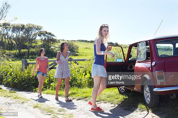 friends walking to a car - lane sisters stock photos and pictures