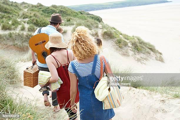 friends walking to beach through dunes. - sac porté épaule photos et images de collection