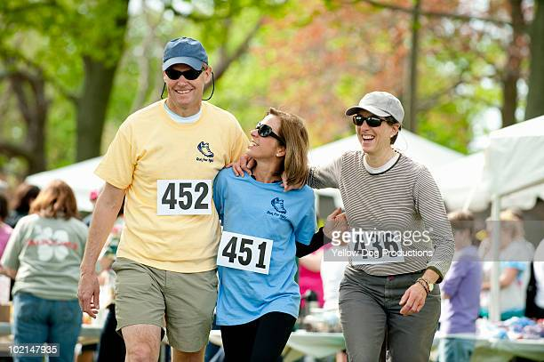 friends walking together at a charity running race - salem massachusetts stock pictures, royalty-free photos & images
