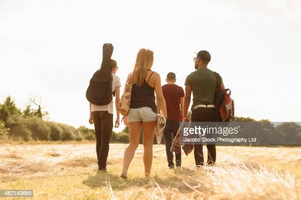 Friends walking together in rural field