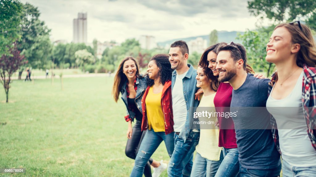 Friends walking together in the park : Stock Photo