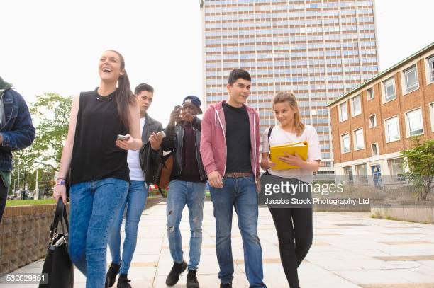 Friends walking together in urban courtyard
