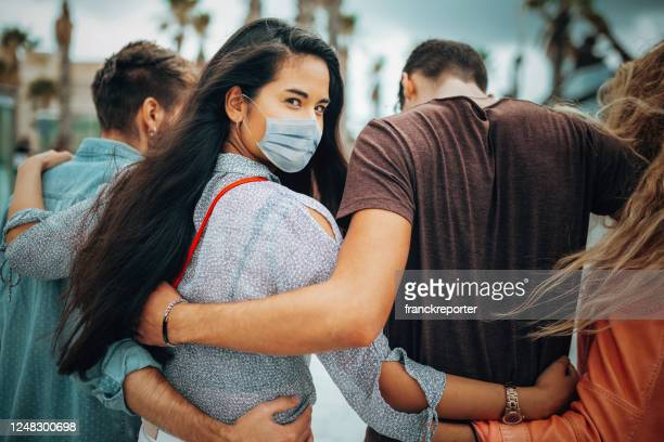 friends walking together wearing the face mask - arm in arm stock pictures, royalty-free photos & images