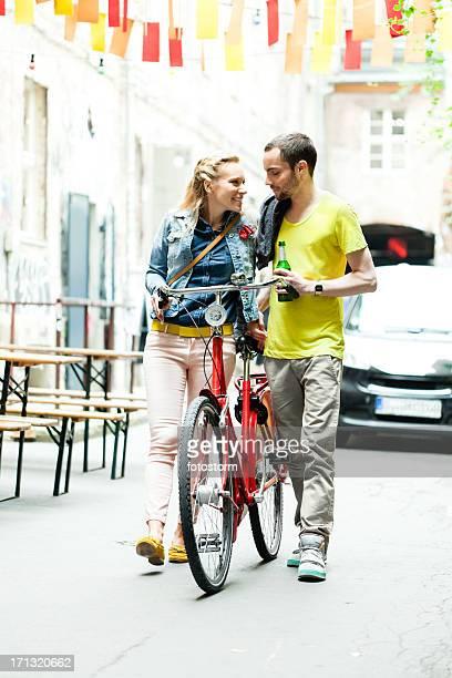 Amigos caminando juntos joven empujando en bicicleta,
