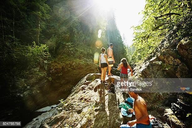 Friends walking up boulder overlooking river