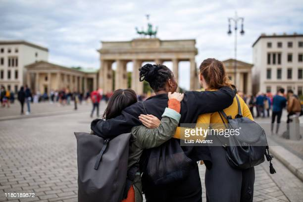 friends walking with arms around against brandenburg gate - female friendship stock pictures, royalty-free photos & images