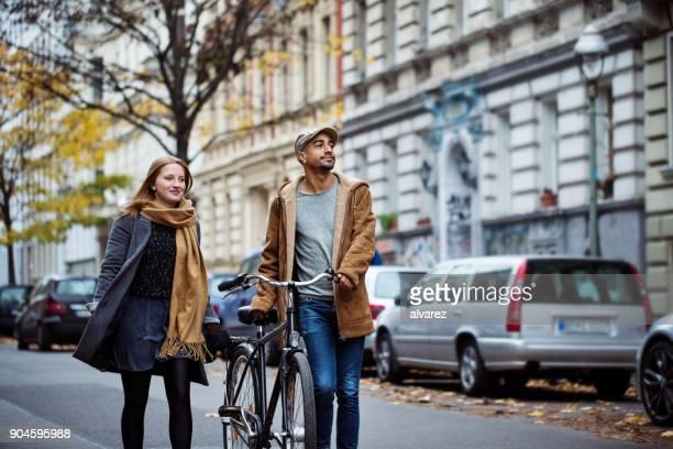 freunde gehen mit zyklus auf der straße im winter - gehen stock-fotos und bilder