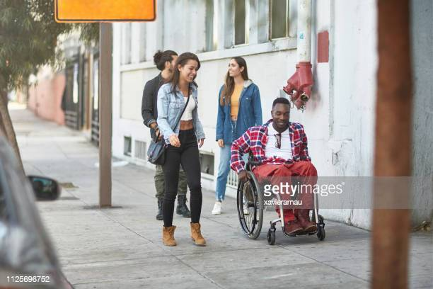 friends walking with disabled man on sidewalk - accessibility stock pictures, royalty-free photos & images