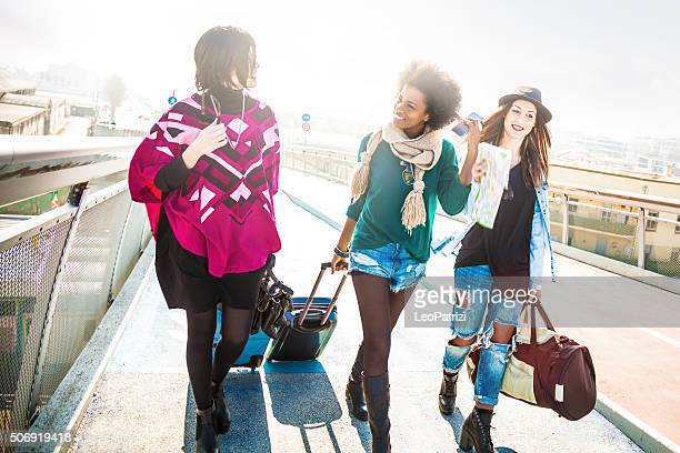 Friends walking with luggages starting an awesome trip