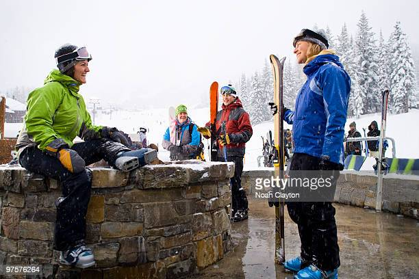 Friends warm up by firepit on ski vacation