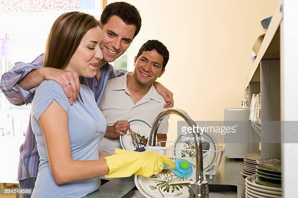 friends washing dishes - gummihose stock-fotos und bilder