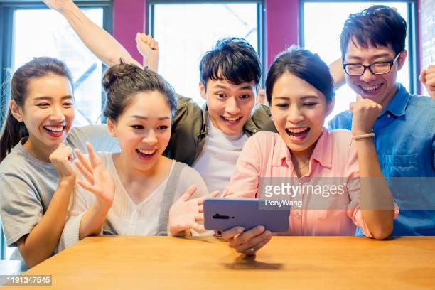 友人は電話でボールゲームを見ます - 対戦 ストックフォトと画像