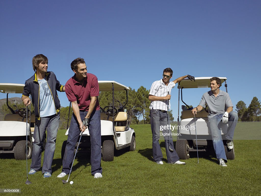 Friends Watching a Casually Dressed Young Man Preparing to Take a Golf Swing : Stock Photo