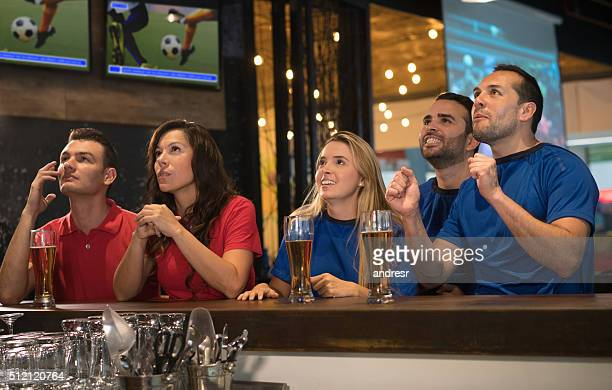 Friends watching a football game at a sports bar