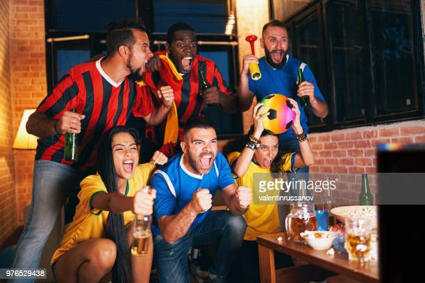 Friends watching a football match on TV