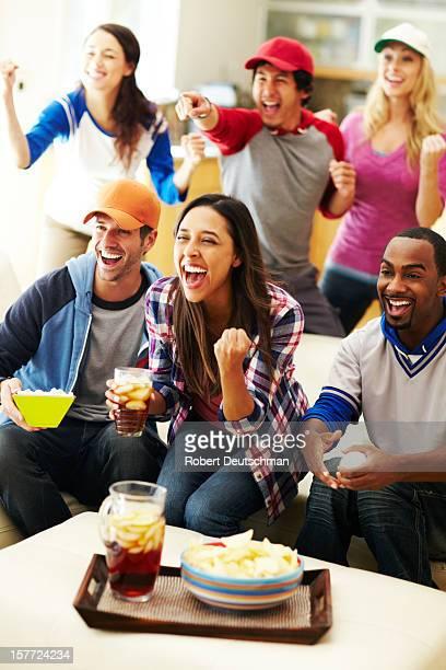Friends watching baseball and cheering.