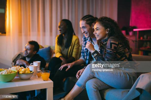 friends watching comedy movie at home - comedy film stock photos and pictures