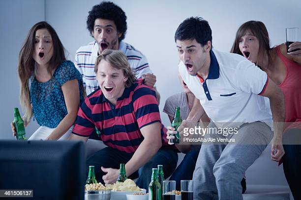Friends watching exciting sports match on television together