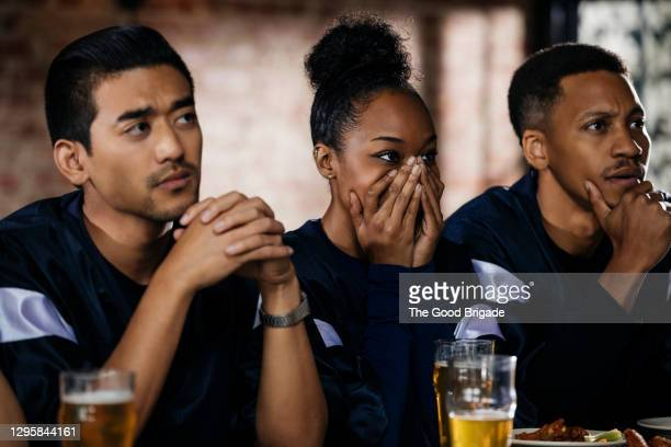 friends watching football game at bar - defeat stock pictures, royalty-free photos & images