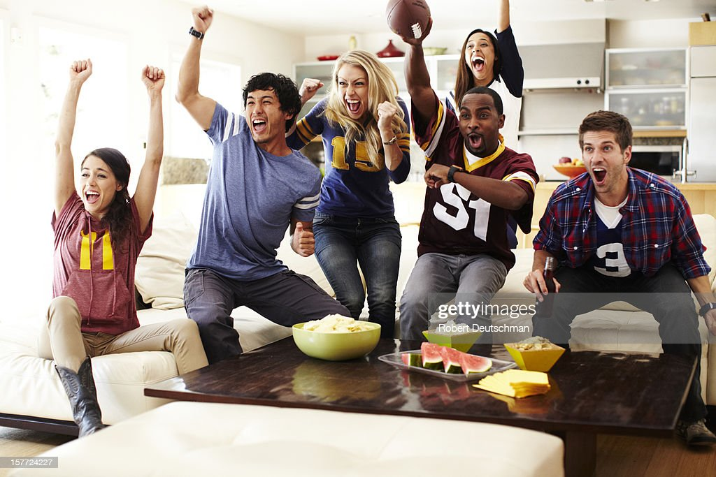 Friends watching football in living room. : Stock Photo