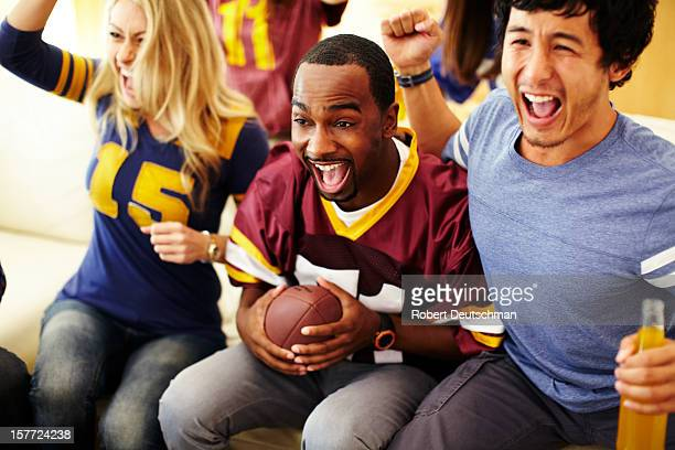 friends watching football in living room. - american football sport stock pictures, royalty-free photos & images