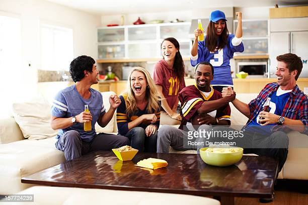friends watching football in living room - amerikanischer football stock-fotos und bilder