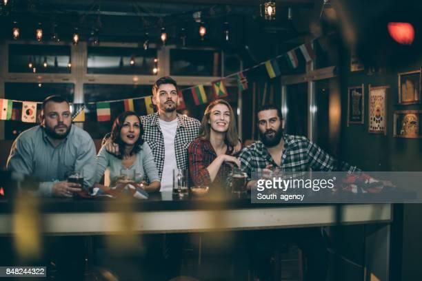 Amigos, assistindo o jogo no pub