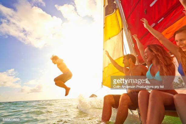 Friends watching man jump from sailboat into ocean