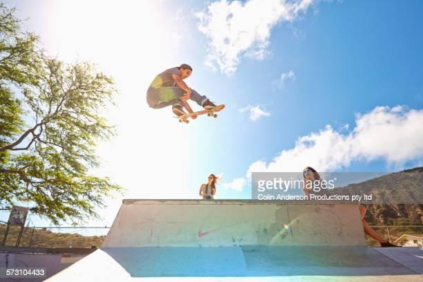 Friends watching man performing trick in skate park
