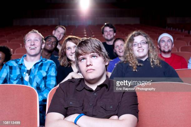 friends watching movie in theater - tensed idaho stock photos and pictures