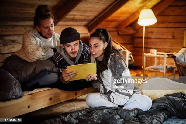 friends watching movie over digital tablet while relaxing in cottage - arts culture and entertainment stock pictures, royalty-free photos & images