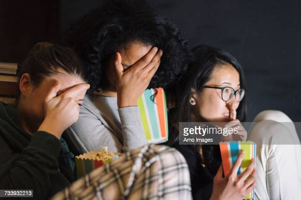 friends watching scary movie covering eyes - florence douillet photos et images de collection