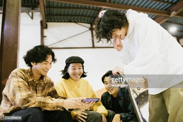 friends watching skateboarding videos. - adult videos japan stock pictures, royalty-free photos & images
