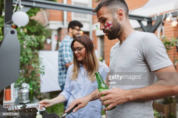 friends watching soccer game on big screen in backyard - england flag stock photos and pictures