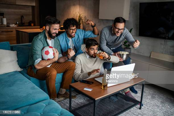 friends watching sport on lap top - champions league trophy stock pictures, royalty-free photos & images