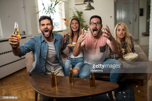 friends watching sport on tv. - champions league trophy stock pictures, royalty-free photos & images