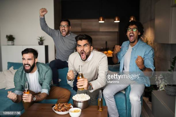 friends watching sport on tv. - sports stock pictures, royalty-free photos & images
