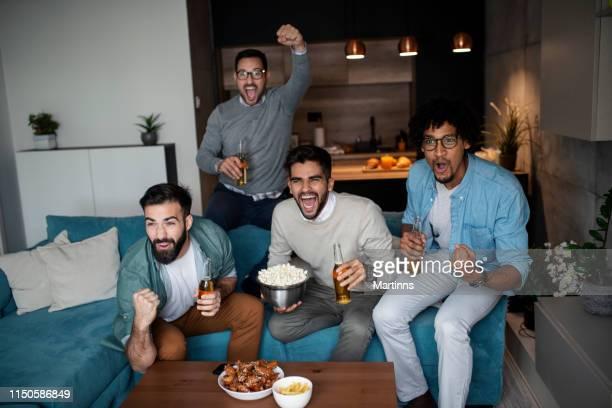 vänner tittar på sport på tv. - friendly match bildbanksfoton och bilder