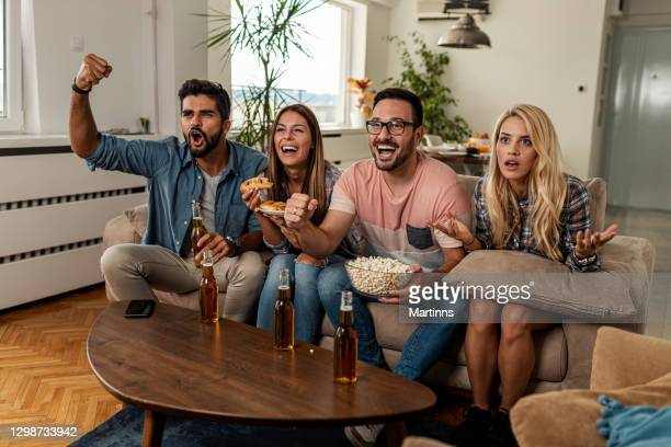 friends watching sport on tv - champions league trophy stock pictures, royalty-free photos & images