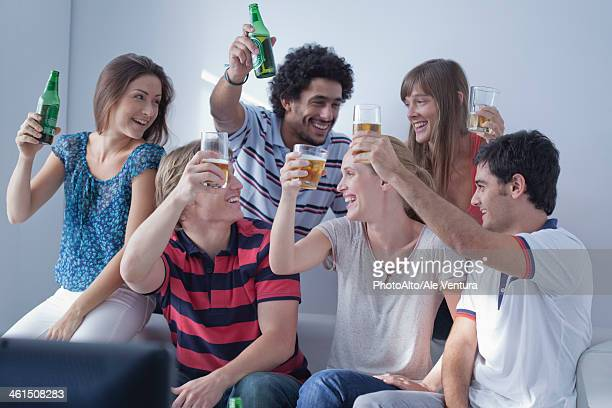 Friends watching sports match on television together celebrate team's victory