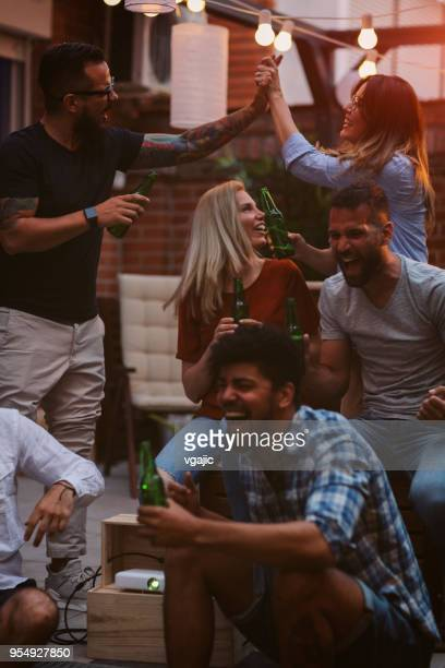 friends watching sports on big screen in backyard - vertical stock pictures, royalty-free photos & images