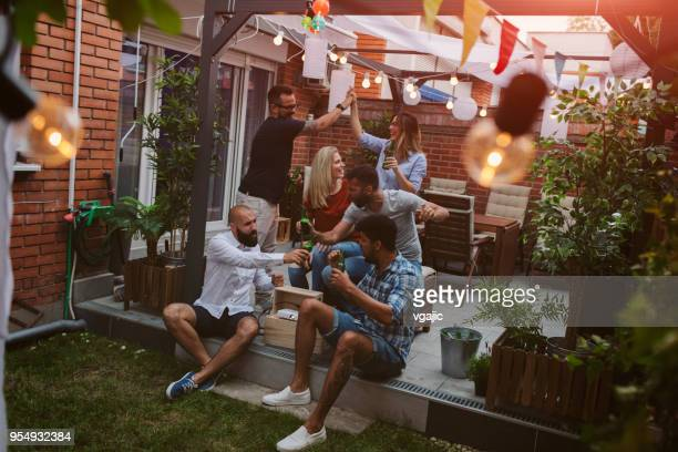 friends watching sports on big screen in backyard - medium group of people stock pictures, royalty-free photos & images