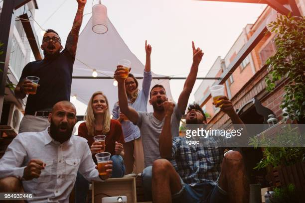 friends watching sports on big screen in backyard - match sport stock pictures, royalty-free photos & images