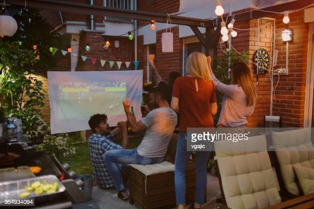 友人の家の裏庭に大画面でスポーツ観戦 - プロジェクター ストックフォトと画像