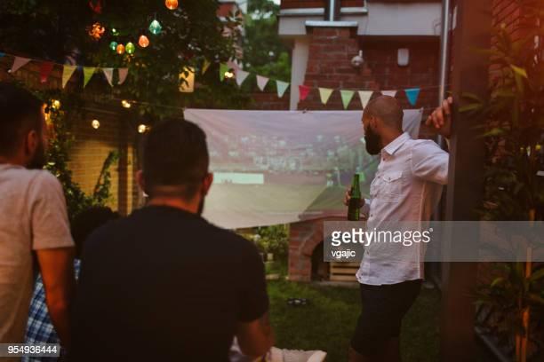 vrienden kijken naar sport op groot scherm in de achtertuin - sports round stockfoto's en -beelden