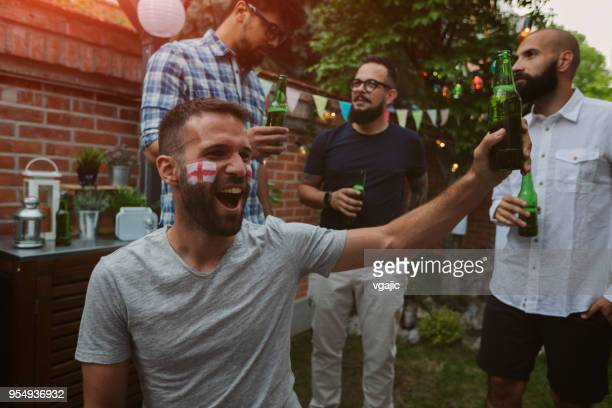friends watching sports on big screen in backyard - england flag stock photos and pictures