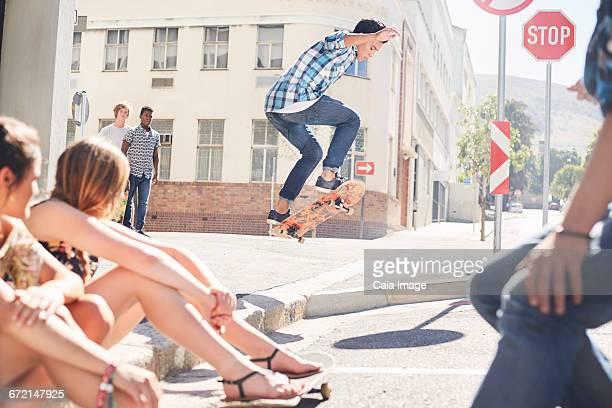 Friends watching teenage boy jumping skateboard at sunny urban corner